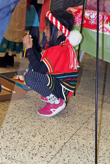 A small child wearing Taiwanese clothing finds a private spot beneath an informational display from which to watch the performances.