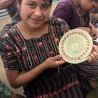 A Mayan Hands basket maker displays her work.
