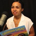 Elizabeth Zunon holding her book, Grandpa Cacao